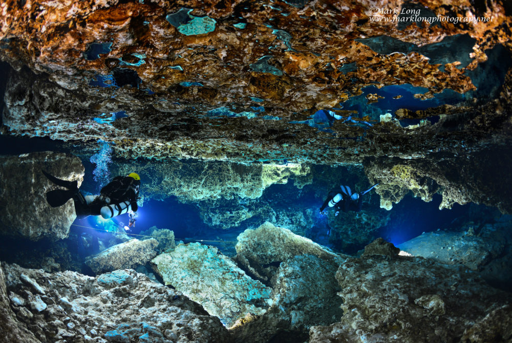 Two divers swim through Devil's Ear Canyon in the Devil's Spring System at Ginnie Springs