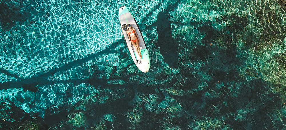 Aerial image of a woman reclining on a paddleboard on top of clear blue spring water.